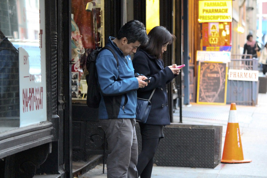 Image by Tina Leggio: two people scrolling through their mobile phones while standing on a street