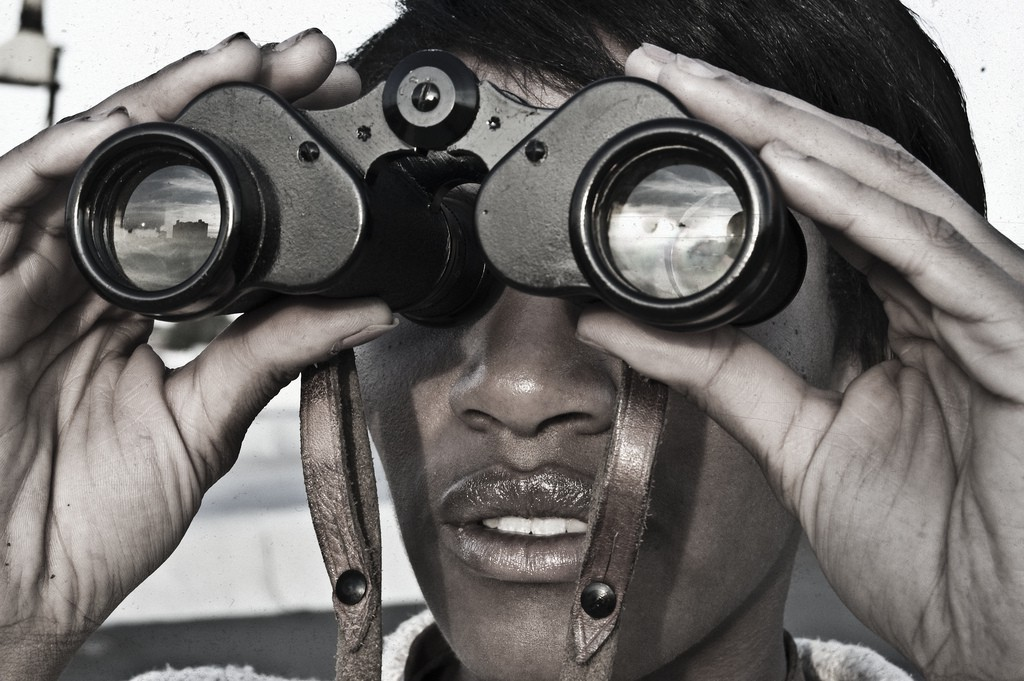 A young man looks through a pair of binoculars. Image by Peter R.