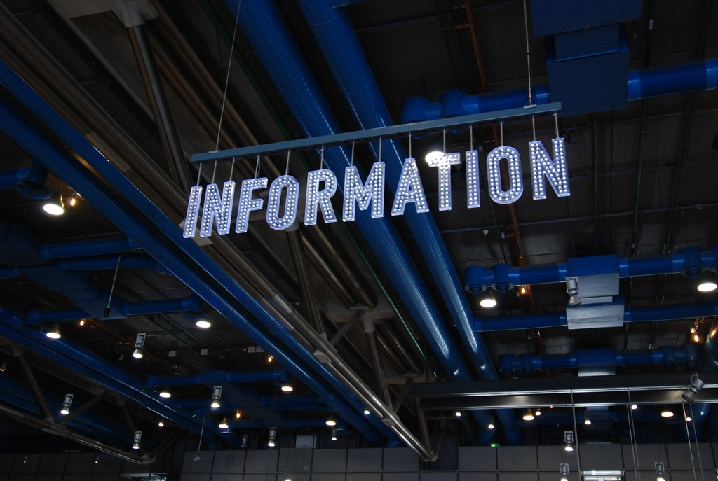 Image by Mor Naaman. A lit up sign suspended from a ceiling, spelling out INFORMATION