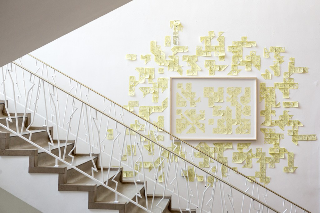 Image by Z33 Art centre: hundreds of yellow post-it notes aranged in shapes on a white wall beside a public stairway