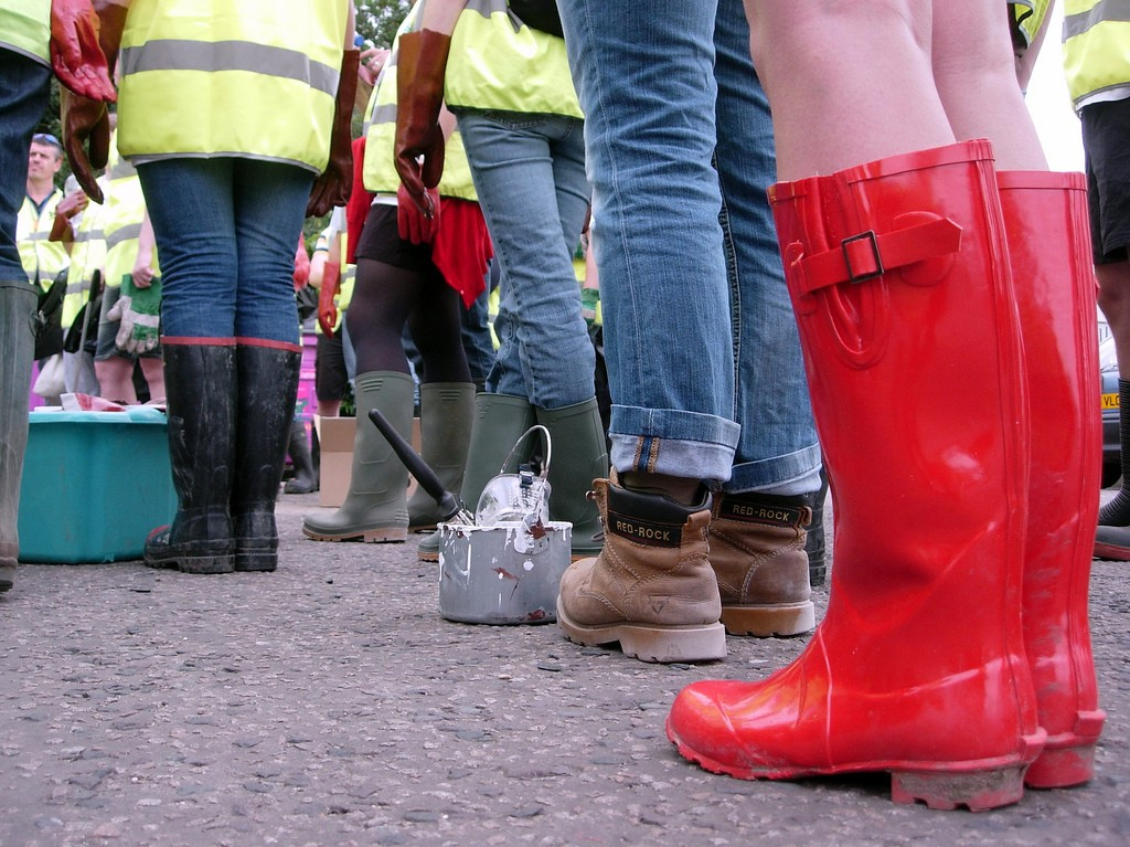 Image by Laura Billings. The feet of four or five people in a queue, together with buckets, brushes and cleaning materials.