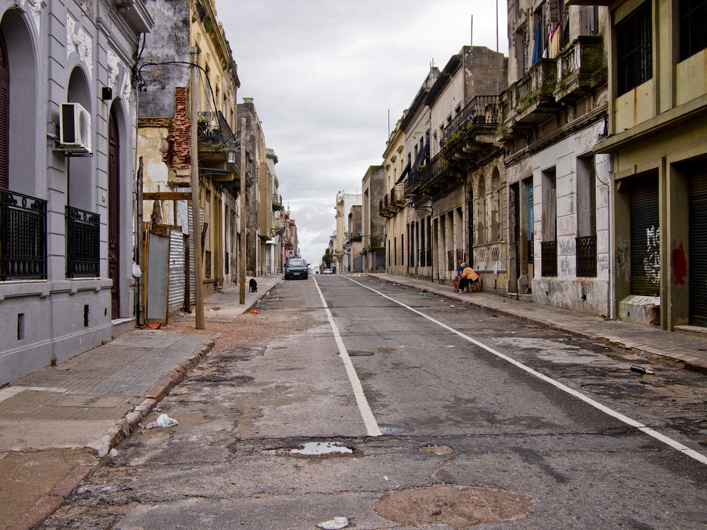 Image by Mardruck. A shot of a potholed street in Montevideo, taken from a low angle, lined by grand but crumbling buildings.