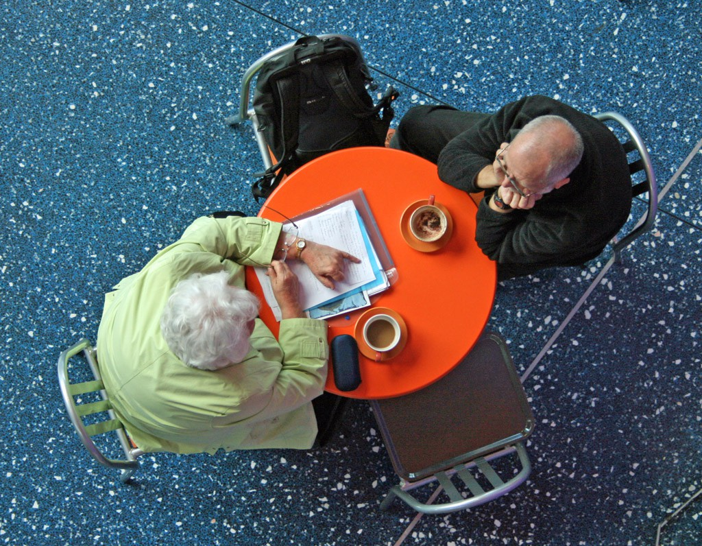 An elderly man and woman sit at an orange table with a stack of papers and some coffee. The image is taken from above.