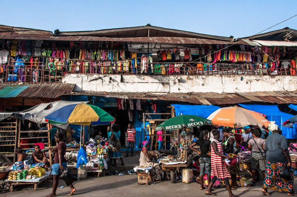 Waterside Stores by Mark Fischer - a colourful picture of small market shops and stalls selling clothing