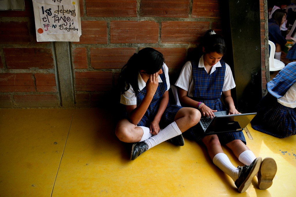 Two schoolgirls sit on the floor in a corridor. One has a laptop open on her lap.