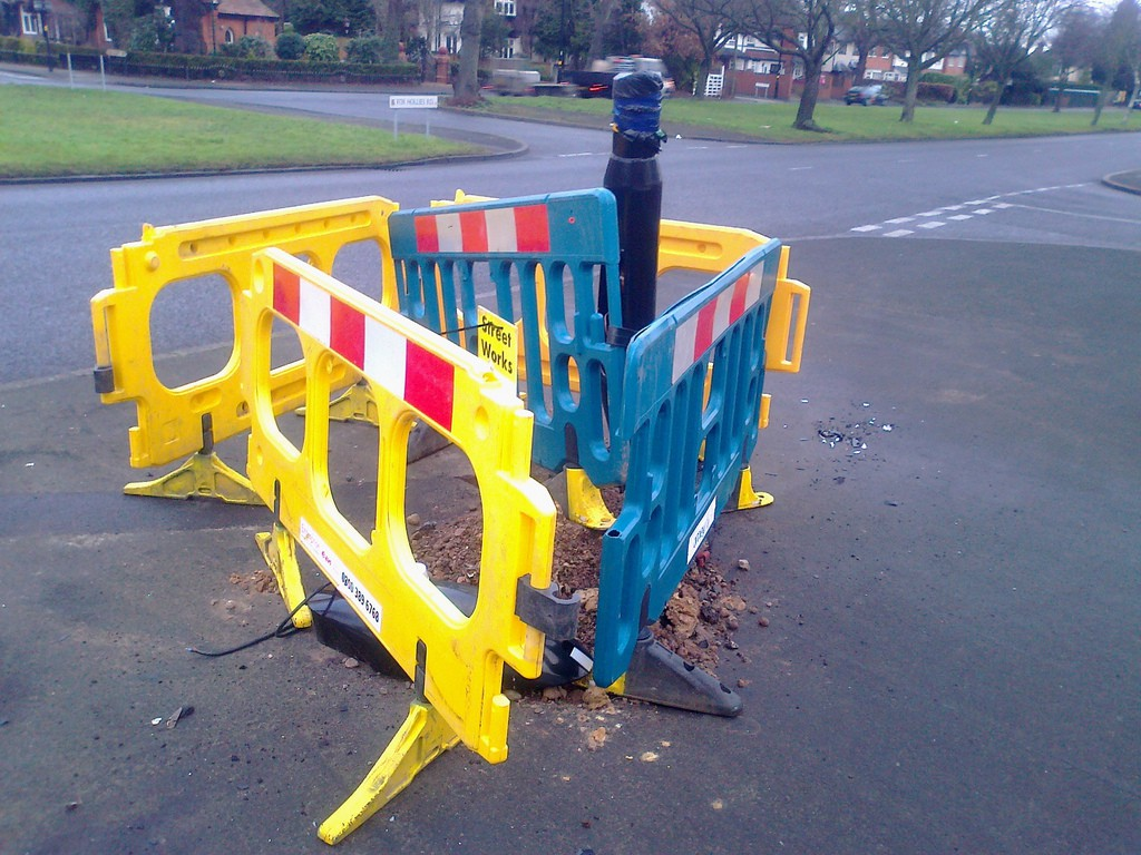 brightly-coloured crash barriers surround a knocked-down lamppost on a wide pavement.