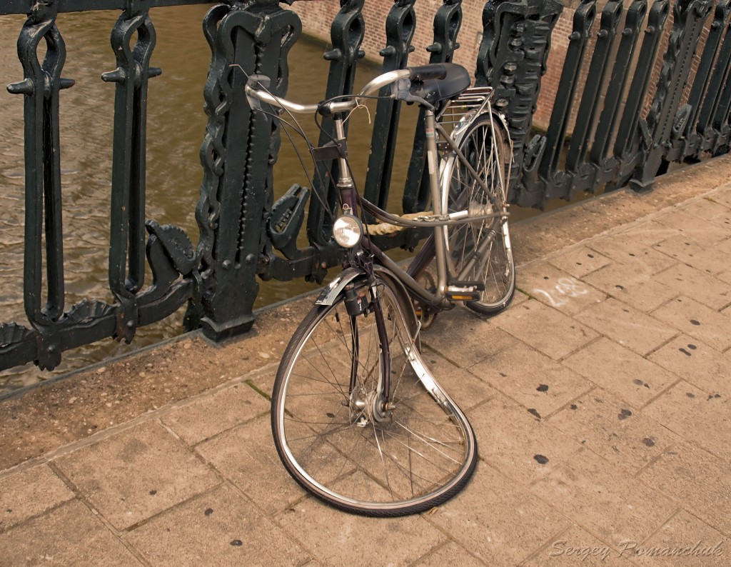 Image by  Сергей Романчук. A bike on a Dutch bridge, with one wheel bent as if a car has run over it.