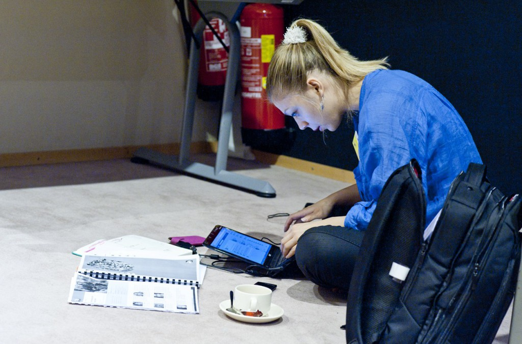 A young woman sits on the floor looking at a tablet and some papers. Image by the European parliament