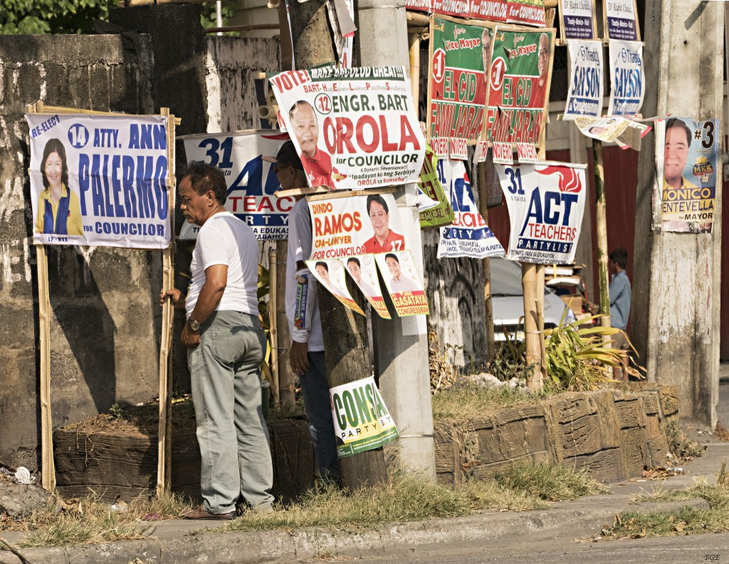 Image by Brian Evans. A man in front of several signs showing election candidates in Bacolod City, Philippines.