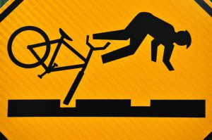 Image by Rob. A road sign showing a cyclist being thrown off his bike because of an uneven road surface