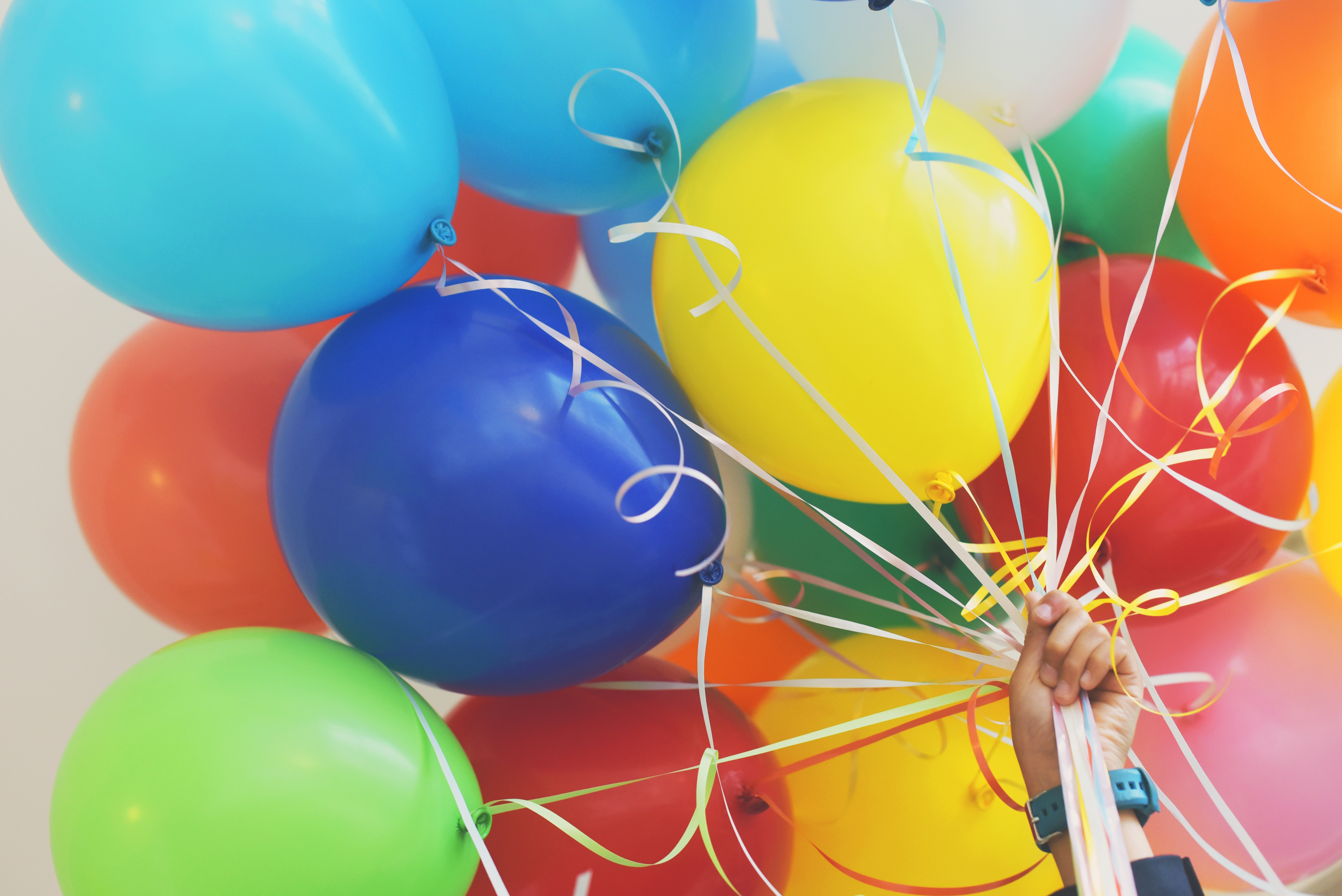 Image by Gaelle Marcel - a hand holding a bunch of balloons