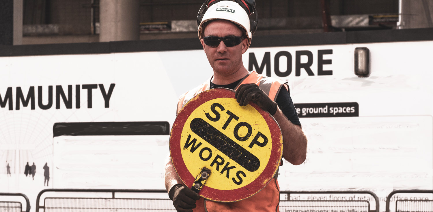 Workman holding a sign saying 'stop works' - via kevin-grieve-974374-unsplash
