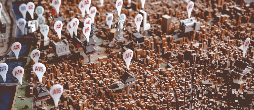 Matching postcodes to administrative areas. Photo by Thor Alvis shows pins in an architectural model of a town.