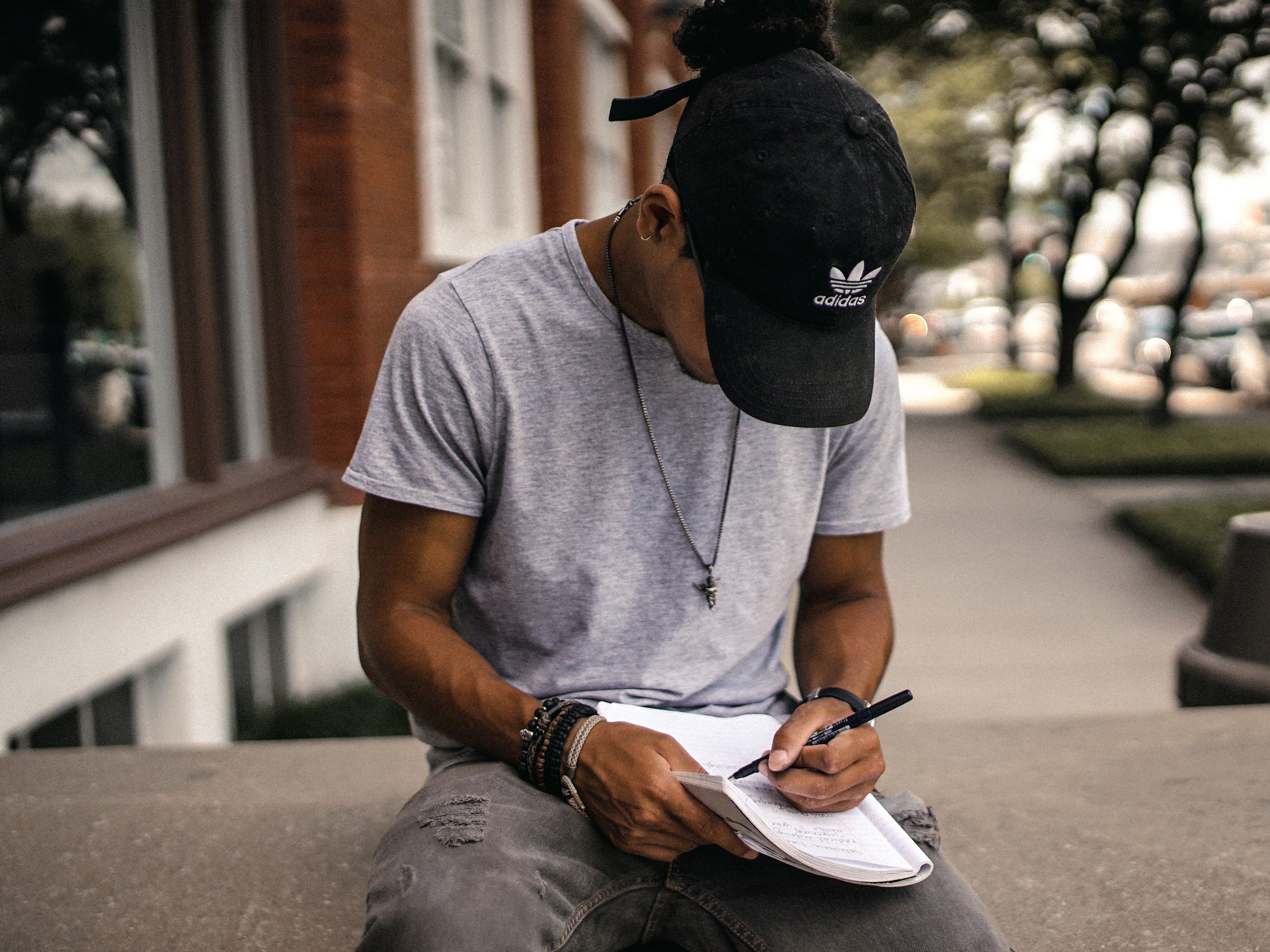 A man writes a letter on a notepad, while sitting in the street