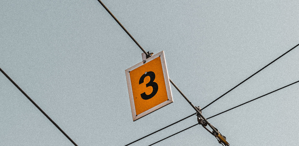 A number 3 sign hanging from some wires against the sky. Image by Max Fuchs