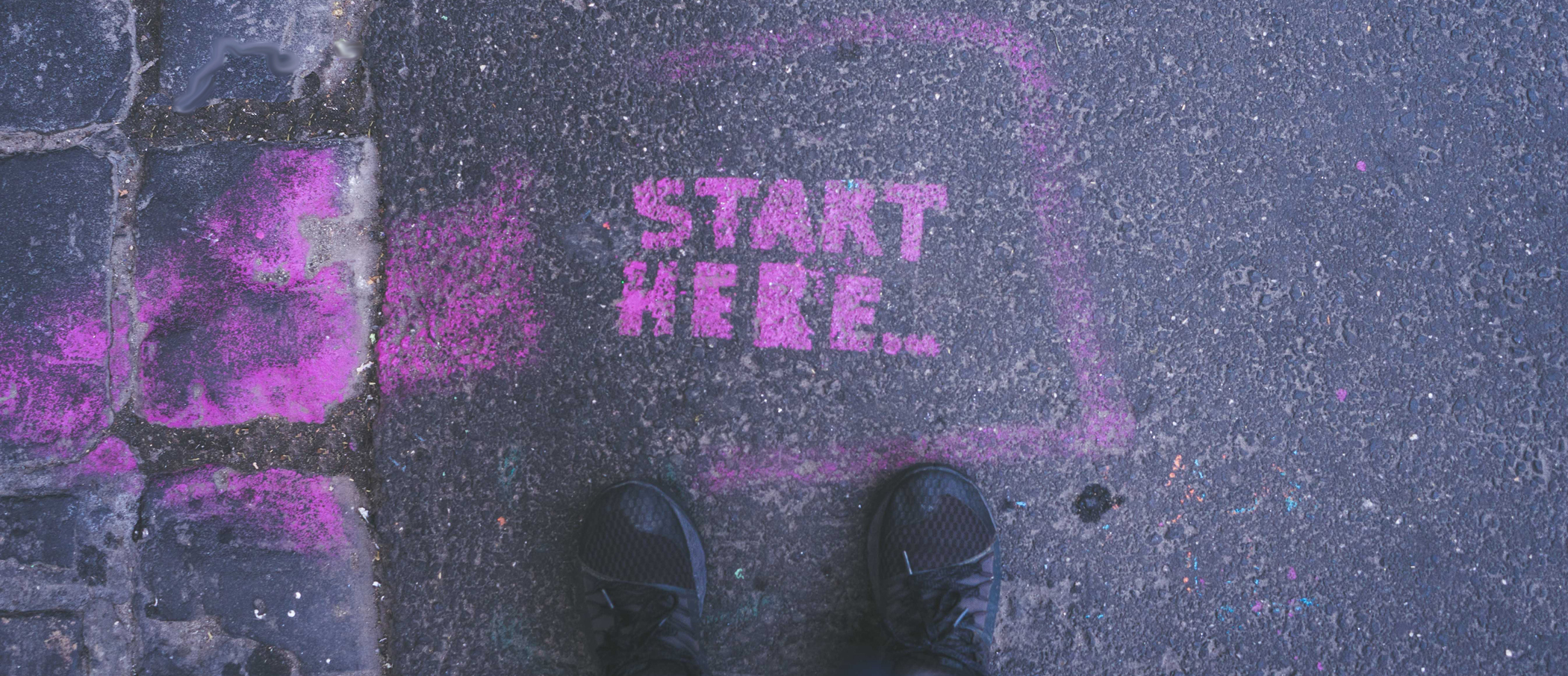 Image by Gia Oris. Feet standing in front of the spray painted pink words ' start here' on the road.