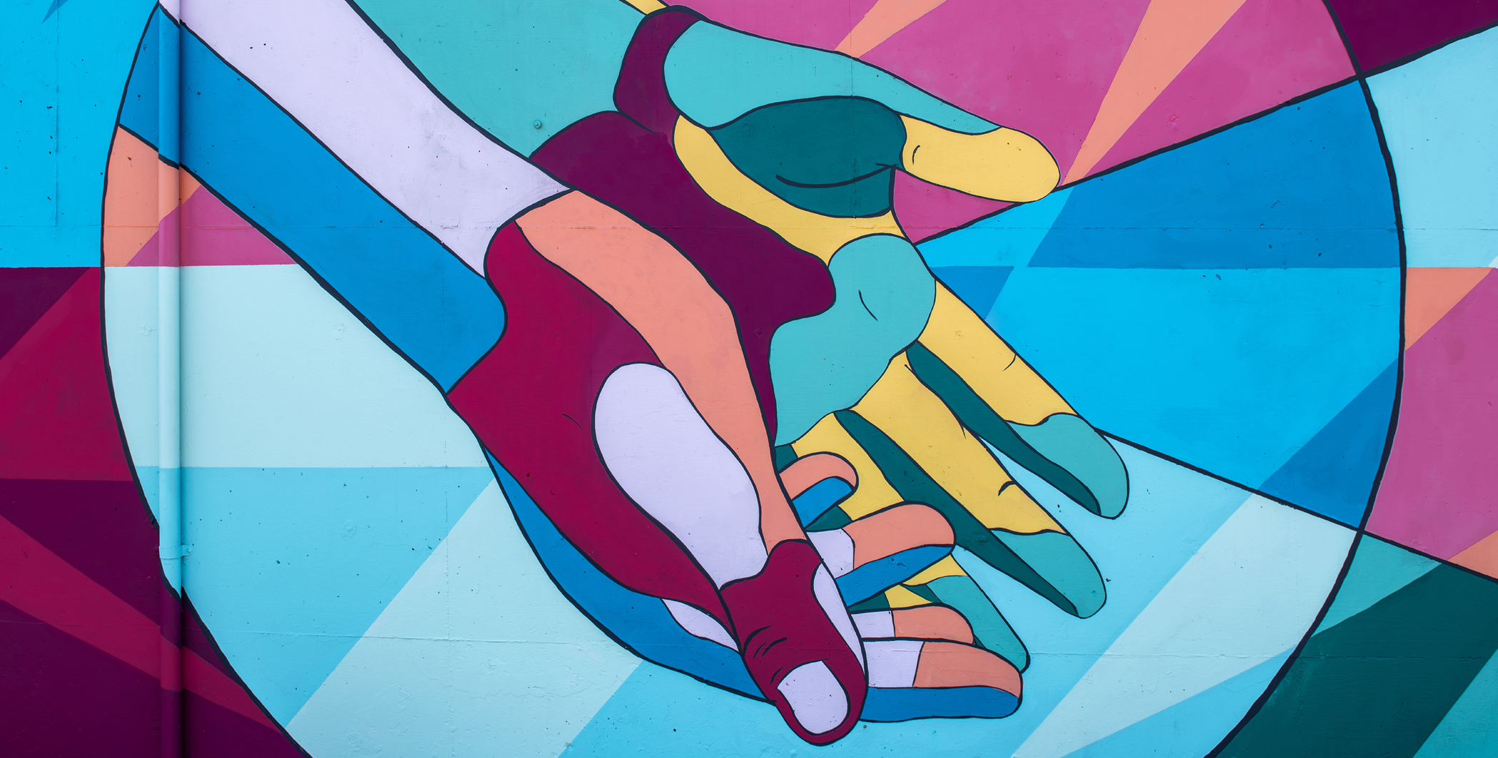 Image by Tim Mossholder: a mural showing some brightly coloured hands