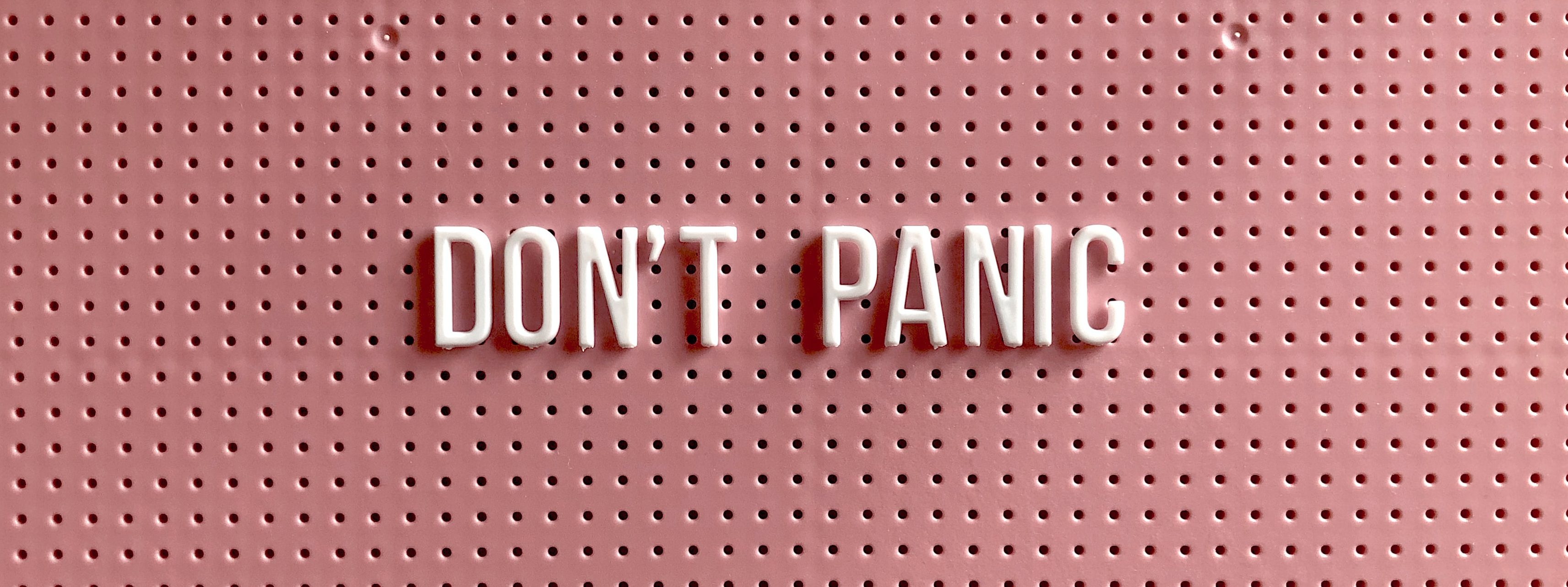 Image by Tonik. White letters on a peg board spell out 'Don't panic'.