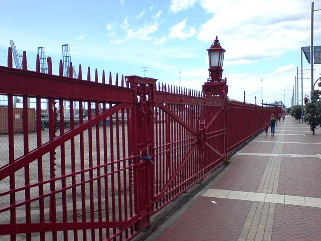 Southern edge (customs border) of Captain Cook wharf, Ports of Auckland, New Zealand. An electric fence is faintly visible behind the historical fence - image by Ingolfson