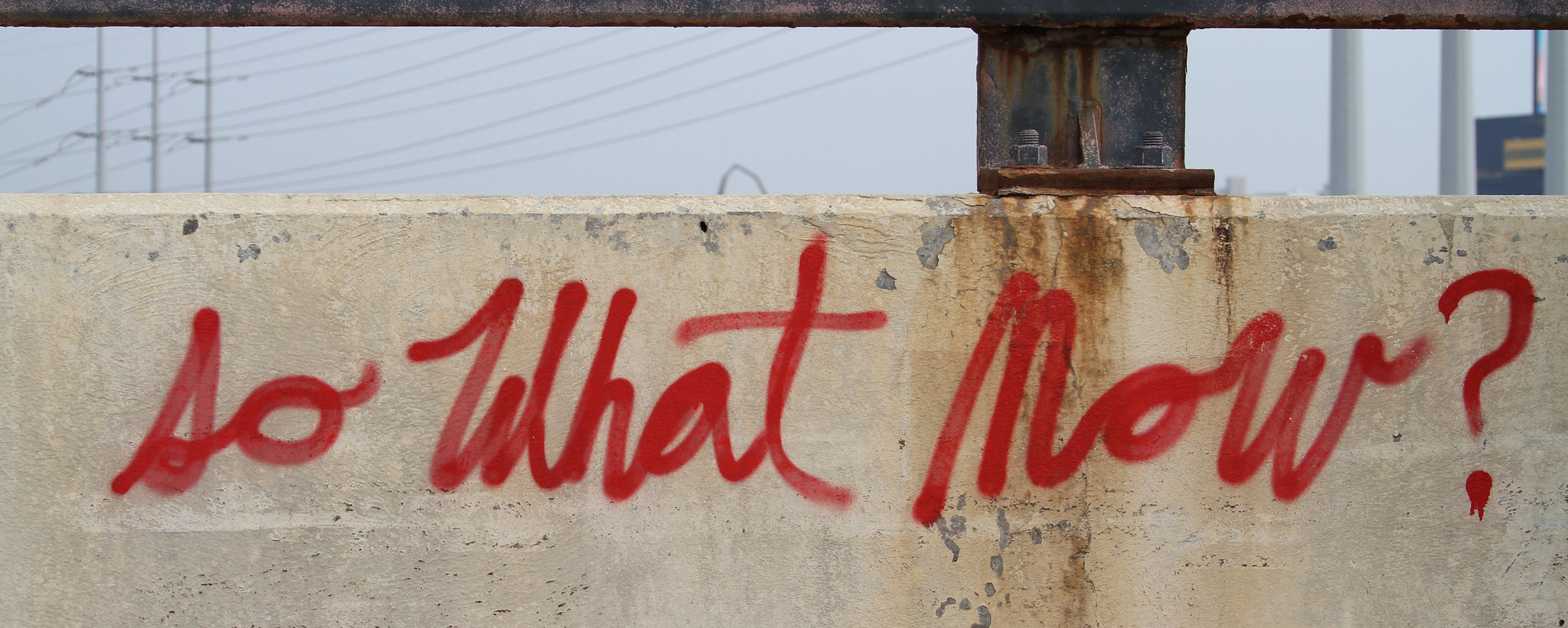 Red graffiti on a wall reading, 'So what now?'. Photo by Andrew Fleming