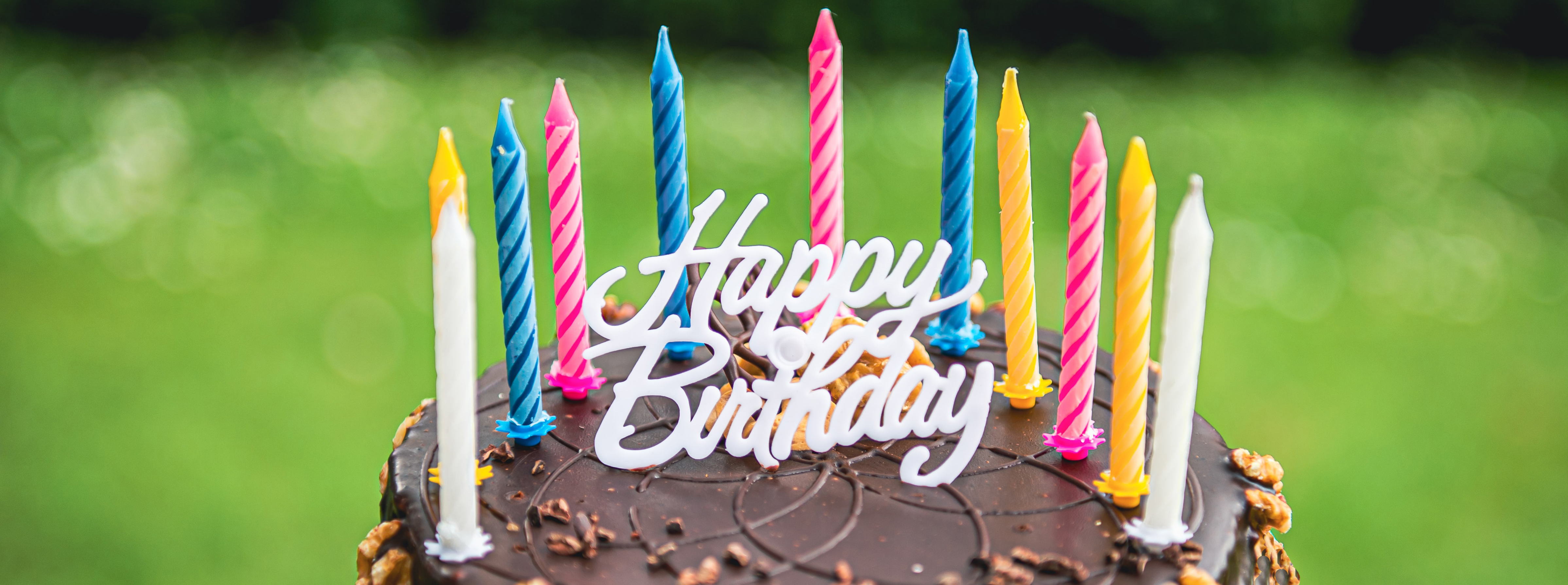 A hand holding a birthday cake with many candles on it, against a green grass background. Photo by Imants Kaziļuns